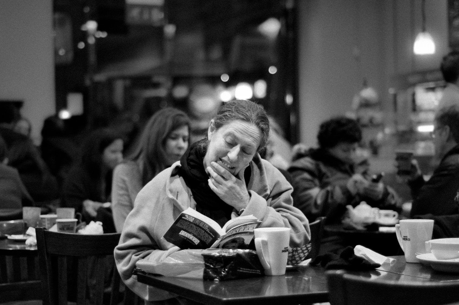 A woman reads a book in a coffee shop