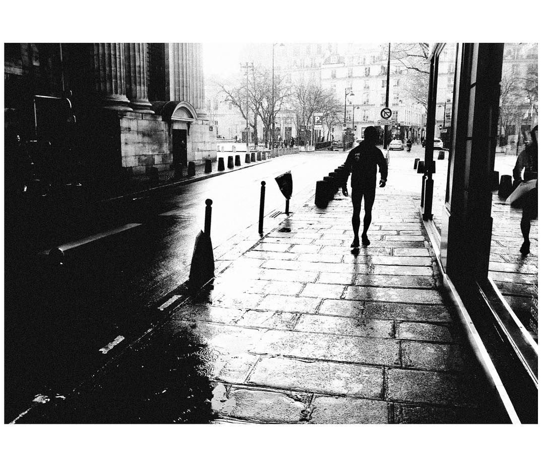 A man carries a long package on a rainy day by St. Sulpice in Paris. Shot with a Ricoh GR2 in black and white by Jay Sennett