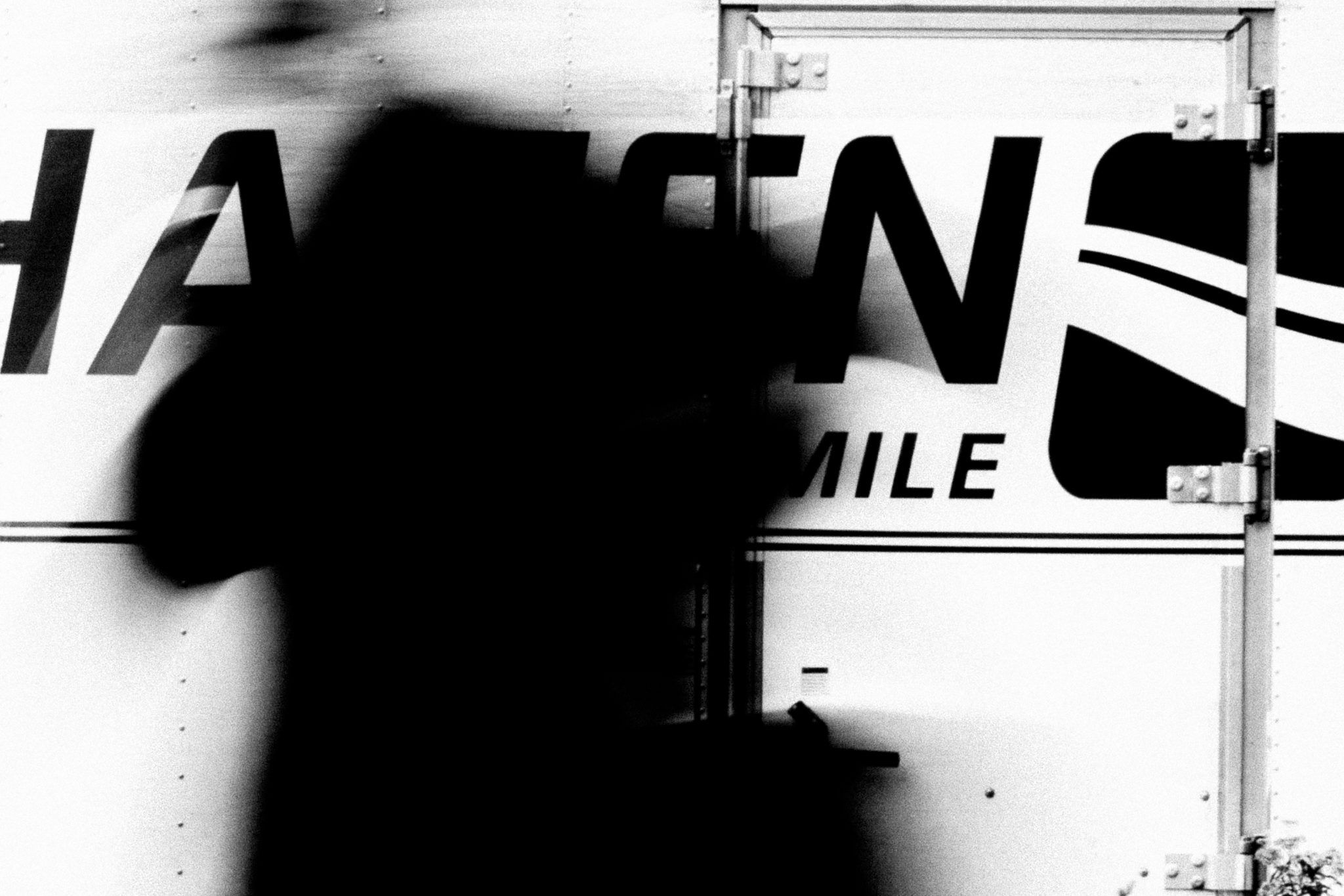 A blurred woman in front of a delivery truck shot by Jay Sennett with a Canon 60D while pulling focus.