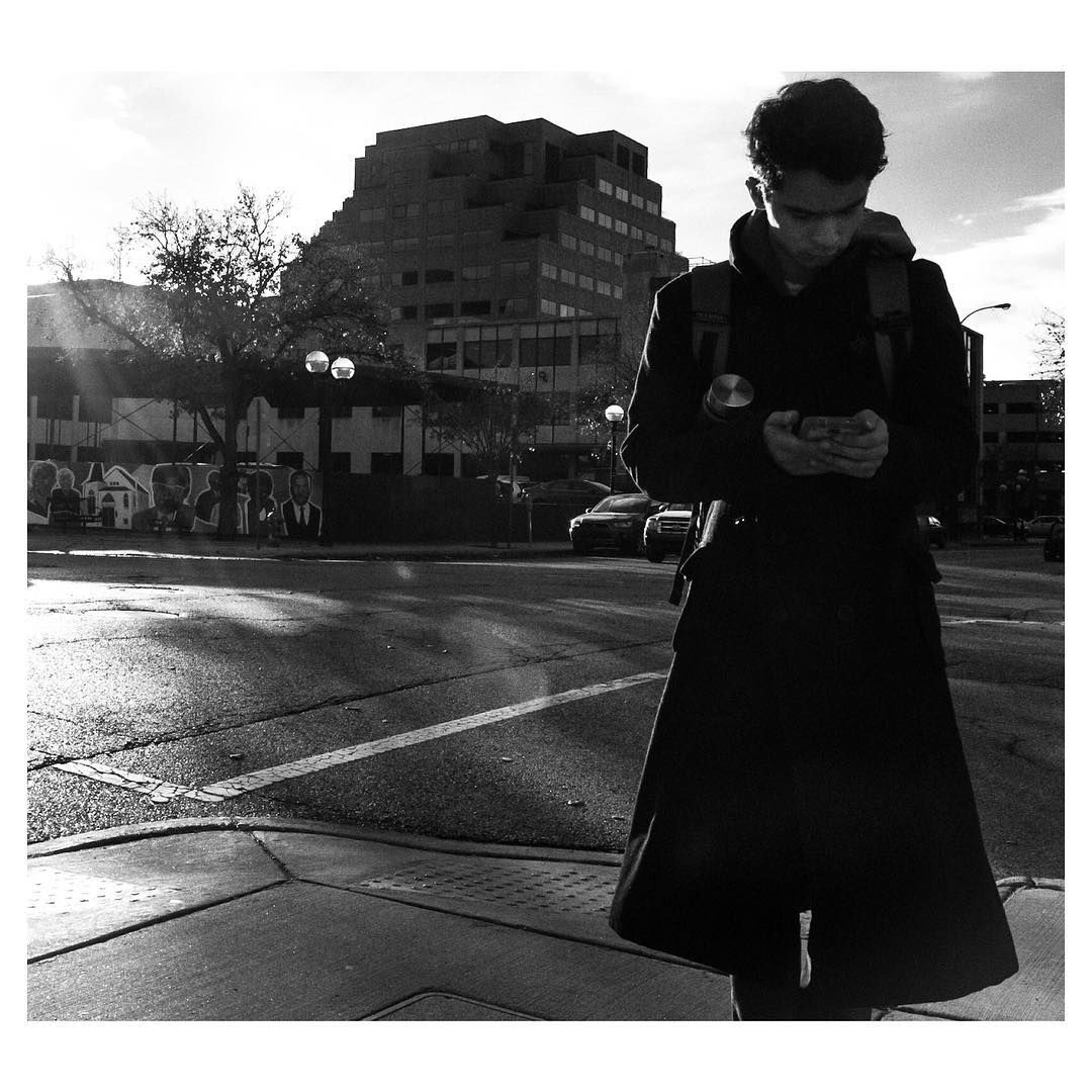 A young man reads his phone on a street corner. Shot by Jay Sennett