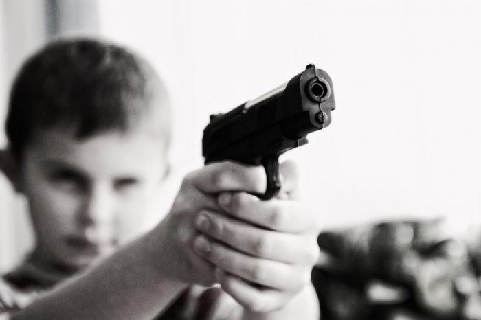 A child holds a pistol