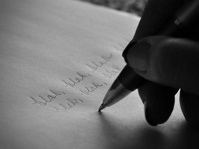 A hand writes blah, blah, blah across a page