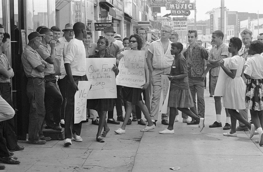 A picketer in front of a Gadsden, Alabama, drugstore turns to answer a heckler during a demonstration, on June 10, 1963. (AP Photo)