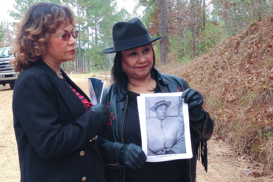 Catherine Walker Jones and Shirley Walker Wright hold a picture of their father, Clifton Walker, and stand on Poor House Road, where he was killed. (Photo by Ben Greenberg)