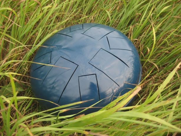 Steel tongue drum laying on the grass