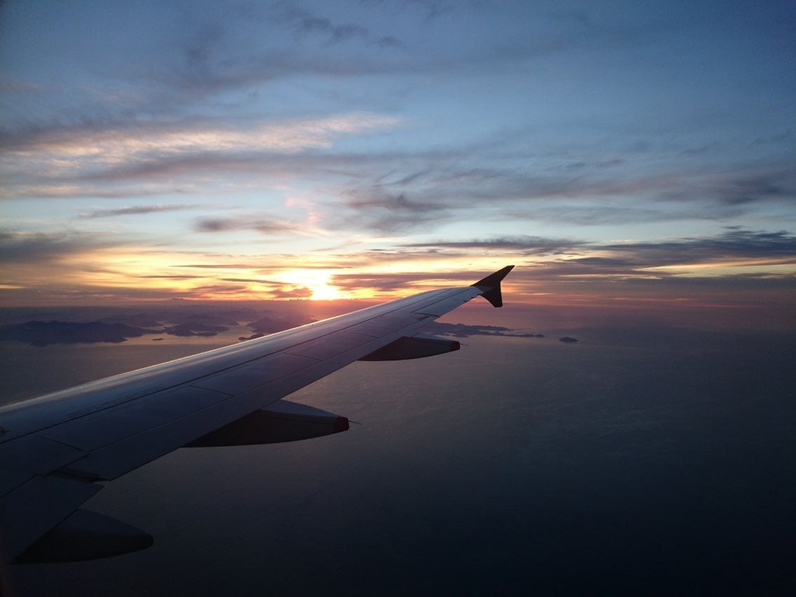 A sunset over marlborough sound, new zealand, with a plane's wing in the foreground.