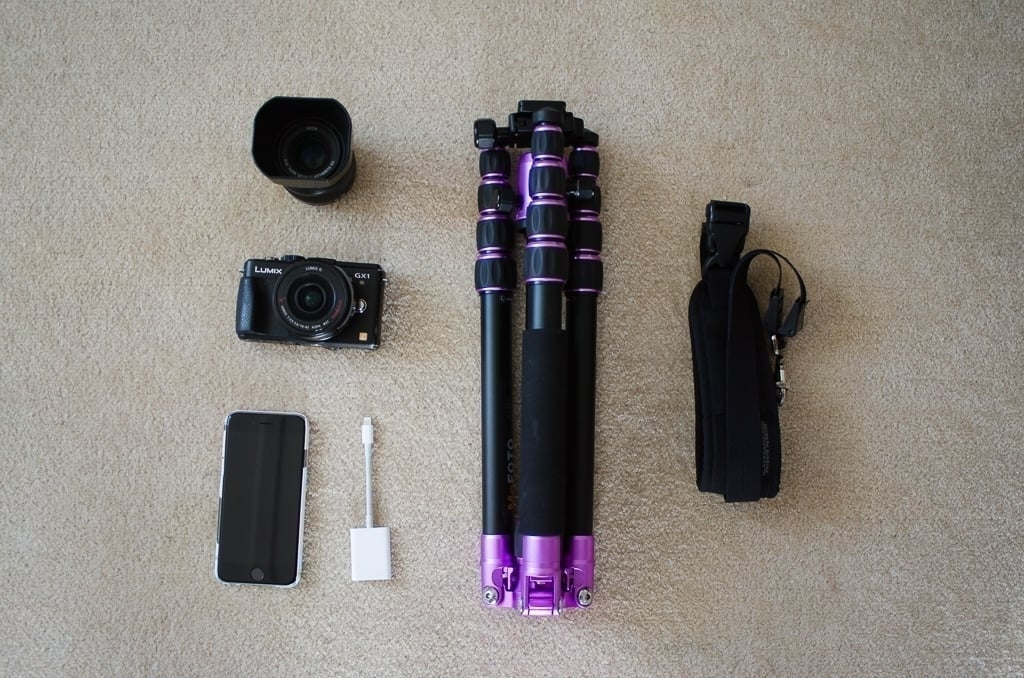 A camera, a spare lens, an iPhone, a tripod, and a carry strap