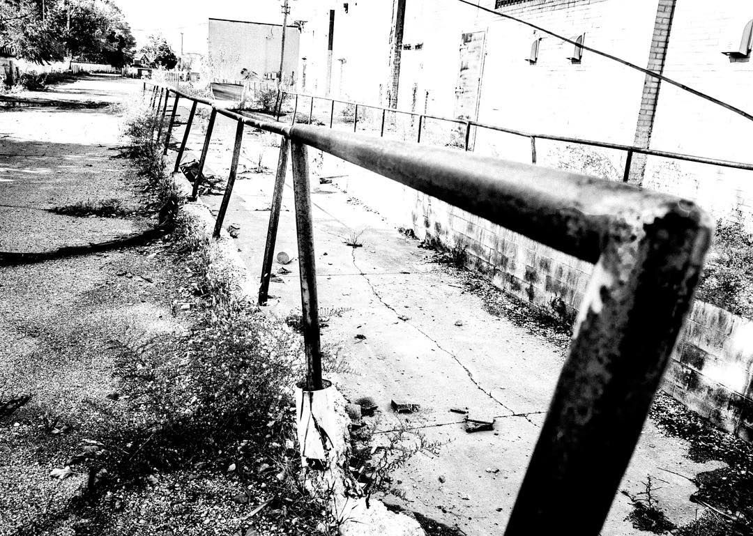 A dilapitated handrail in a decaying shopping mall