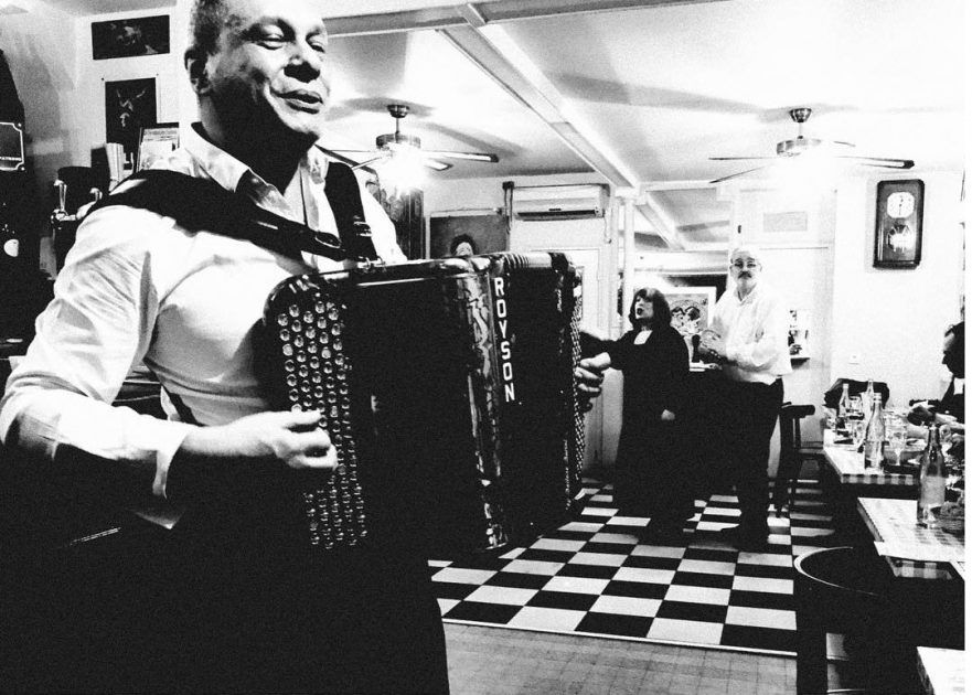 A man plays an accordion in a traditional Bistro. Shot with an iPhone 6 by Jay Sennett