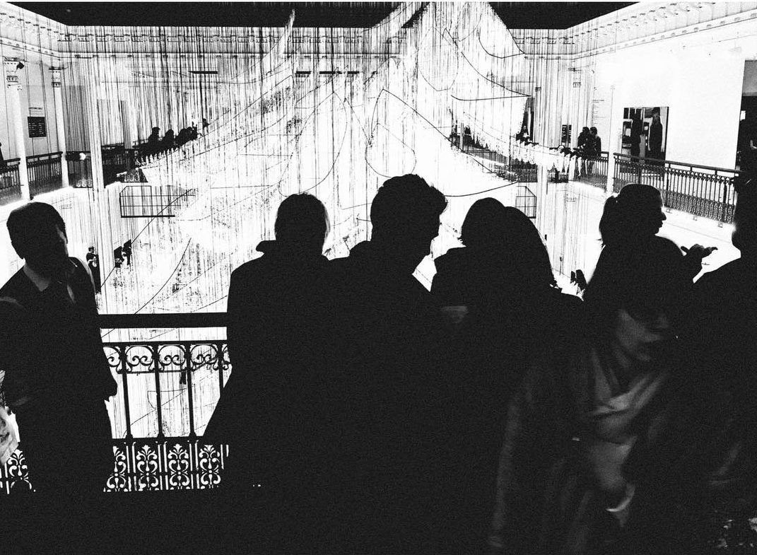 People standing in front of an escalator at Gallerie Lafayette. Shot with an iPhone 6 by Jay Sennett