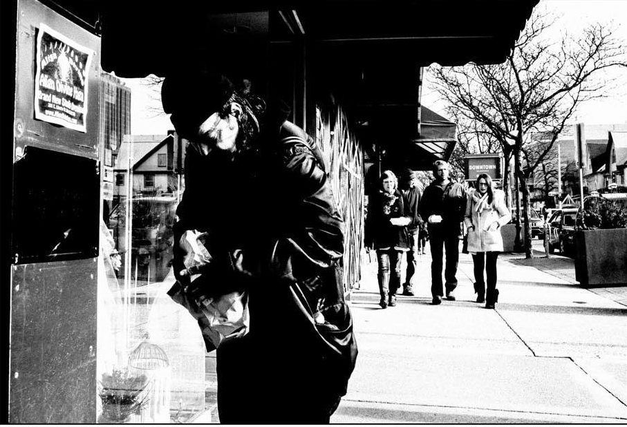 A homeless man rips open a bag filled with burgers. Shot with a Ricoh GR2 by Jay Sennett.