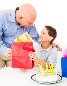 Cute little boy gets a birthday gift from his father. White background.