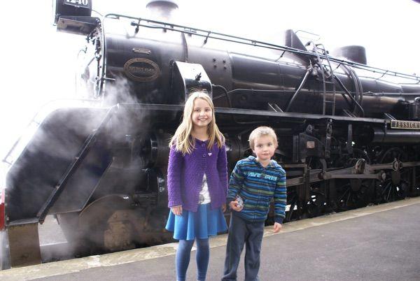 Standing beside steam engine