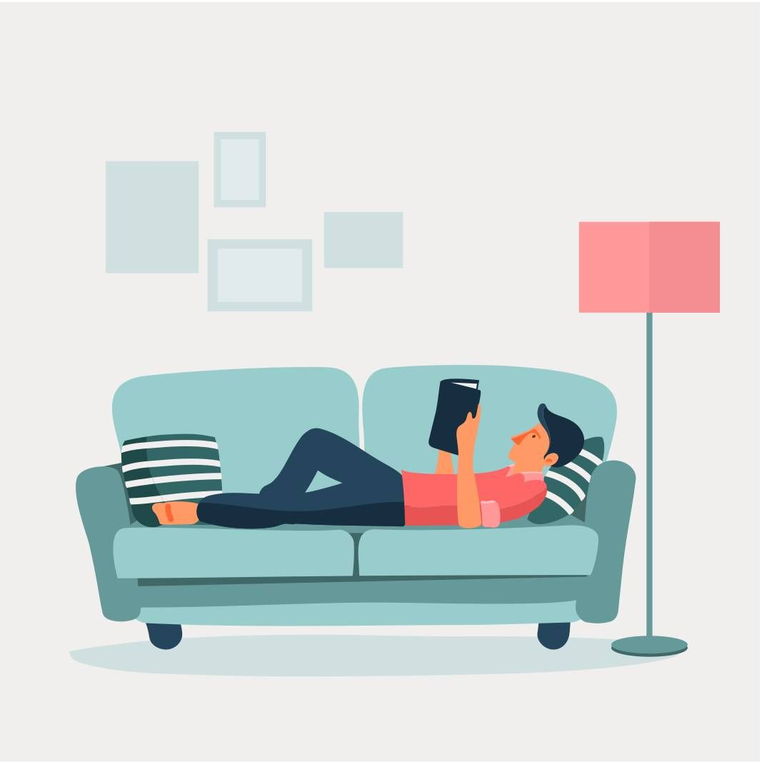 Man lying on a sofa reading a book