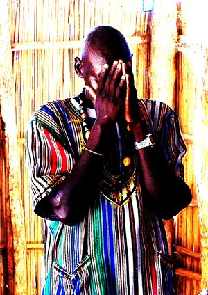 Ugandan man in brightly coloured shirt praying