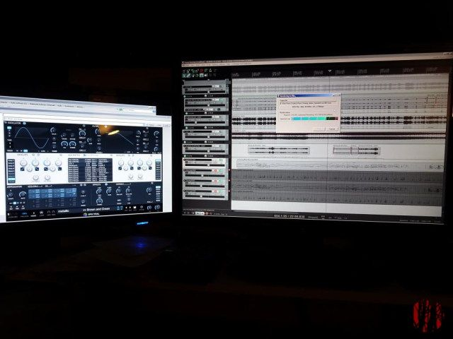 Photo of bright computer screens against a dark background showing music software rendering a project to a sound file