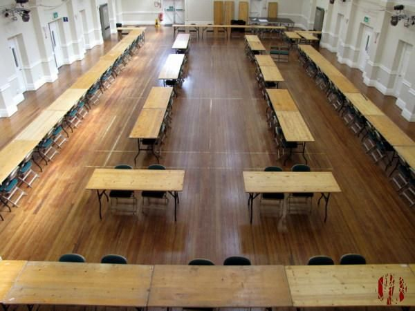 Wooden tables laid out in the Drill Hall Horsham before the arrival of election ballot boxes