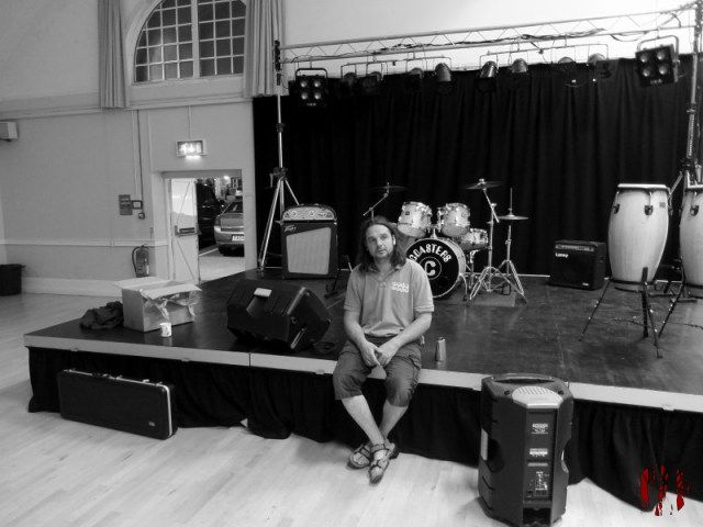 Stage at the Drill Hall set up for a video shoot by the band The Coasters with guitarist Adam sat on the front of it. In black and white.