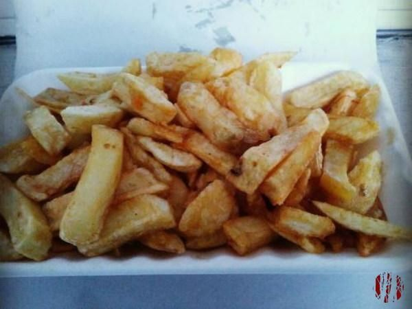 Close up of a portion of chips in polystrene container on greaseproof paper.