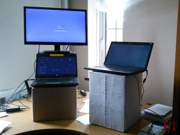 Two laptops and a monitor screen on top of cardboard boxes of varying height to creat a standing desk.