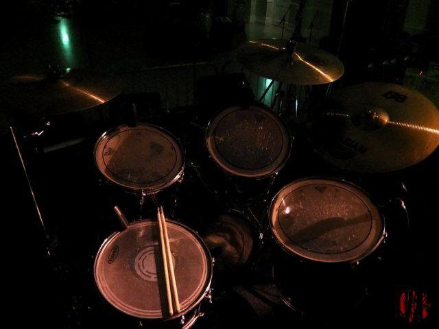 Photograph looking across a drum kit on the stage of the Drill Hall lit by the street lights through a window.