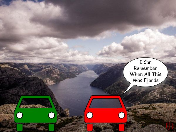 "Two cars are parked overlooking a long narrow glacier cut water way in Norway with one saying, ""I can remember when all this was fjords""."