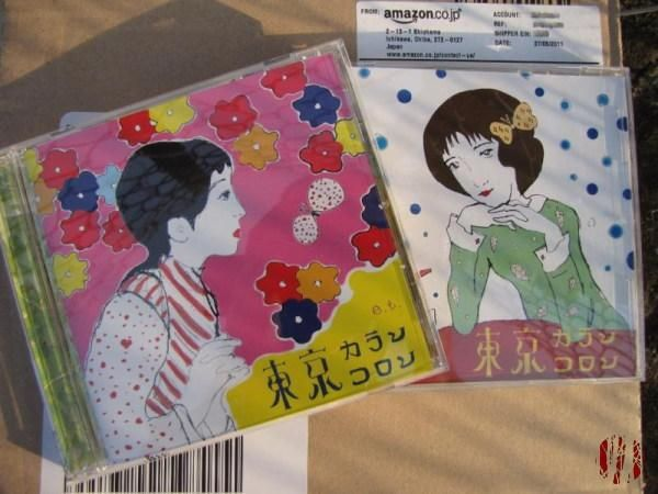 The first two Tokyo Karan Koron CDs on top of the package they arrived in from Japan, itself on a wall with the shadow from a wire linked fence on them.