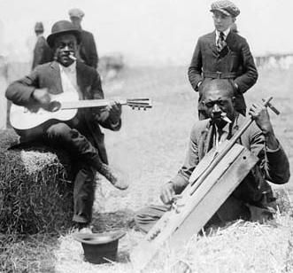 Black American musicians playing kazoos, guitars and home made bass in 1914 sat on bales of hay.