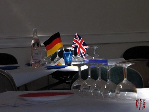 British and German flags seen in a shaft of light in an otherwise blacked out Drill Hall before an event involving school children from the Twin Town of Lage