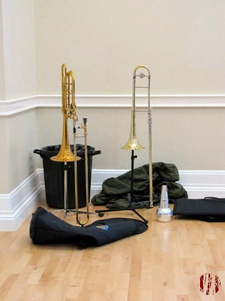 Two trombones on stands in the corner buy a black plastic rubbish bin with bags strewn around them