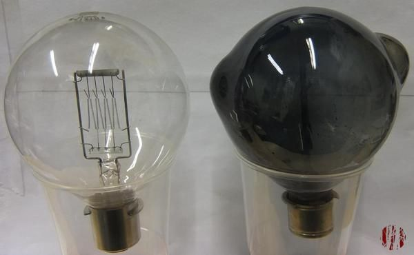 A new bulb for a theatre lantern next to an old bulging and blackened one.