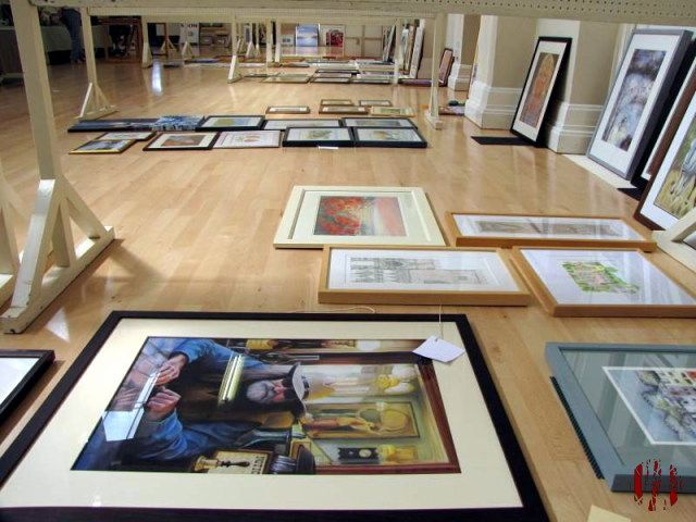 Framed paintings laid out on the floor of a hall ready to be hung on exhibition screens.