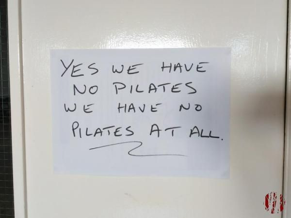 Sign on a door saying 'Yes, we have no pilates' in the style of the World War II song 'Yes, we have no bananas'.