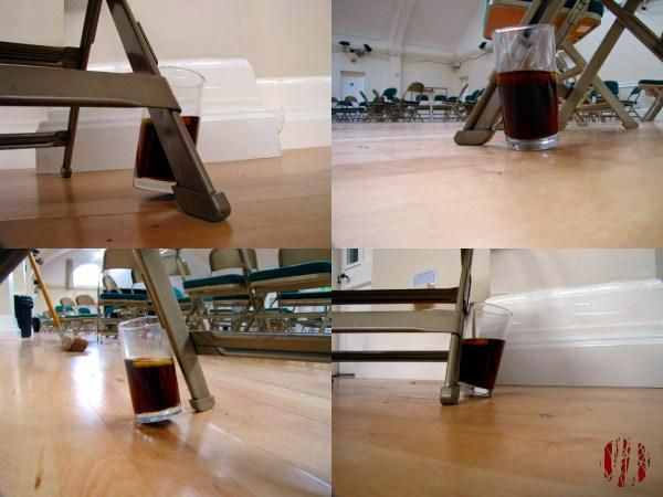 A two thirds full tumbler of cola with slice of lemon lent against a chair leg at a precarious angle seen from from four sides.
