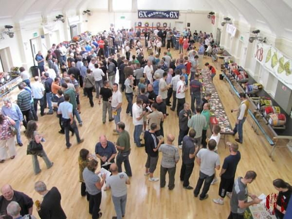 The Main Hall of the Drill Hall with barrels arranged around the sides on staging at one metre height and racking at the far end. In the middle are about 300 drinkers and to the side the Broadwood Morrismen band who can be heard in the clip.