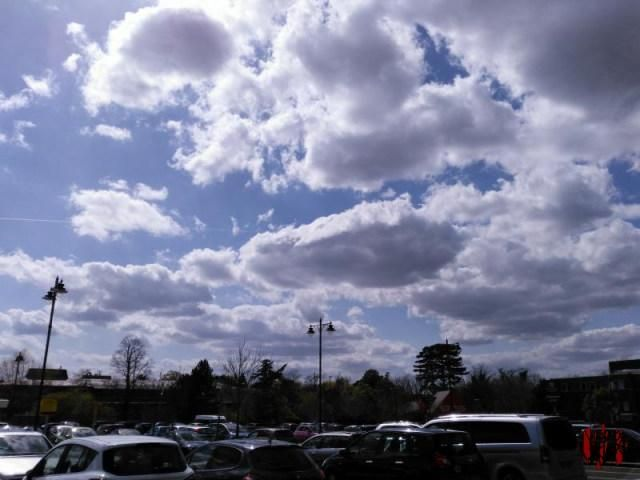 White fluffy clouds with dark undersides against a blue sky above Sainsburys car park in Horsham.
