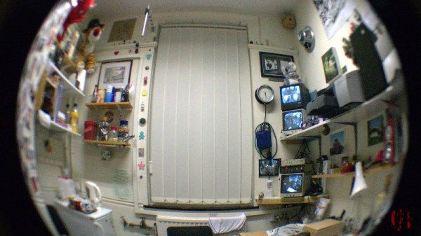 Photograph of my office taken through a fish-eye lens with computer screen, hi-fi, reference books, larger speakers, posters, and miscellaneous tat.