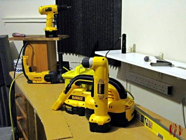 Phtotograph of ongoing work involving four different tools from DeWalt in their distinctive bright yellow. It's a small site hoover, a right-angled drill and mains and battery powered standard drills.