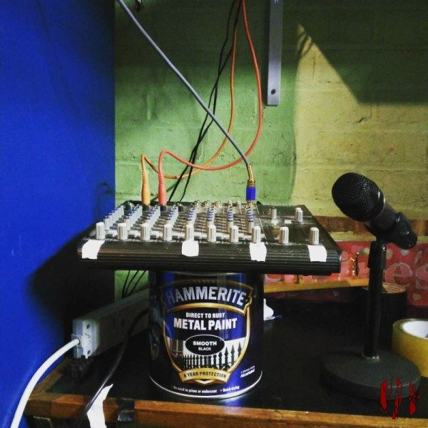 PA small Mackie audio mixer rested on top of a tin of Hammerite paint.