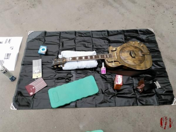 A brass on iron resonator guitar laid on a mat on a flat roof with tools around it