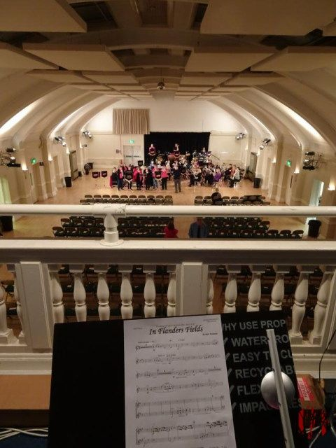 Photo from the balcony of the Drill Hall looking across a music stand with a trumpet part for In Flanders Fields towards Boobs and Brass all ladies Brass Band rehearsing.