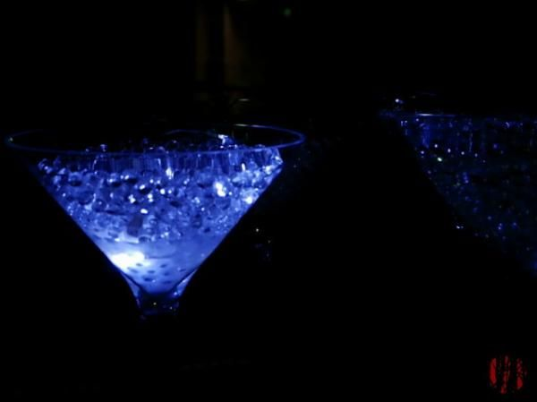 Blue light shines on a glass containing plastic beads