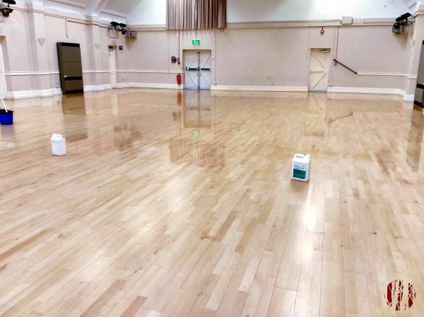 A Hall floor part where through coating with a maintainer sealant with with the part already done shiny and reflecting the lights and roof