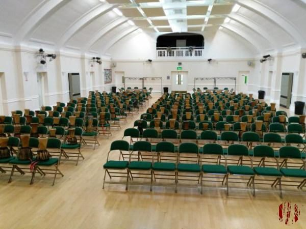 Two hundred or so chairs with djembes on them laid out in the Drill Hall Horsham.