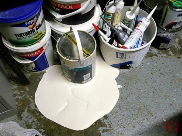 A pool of Olympic Lily (posh magnolia) vinyl silk paint around the base of a can that has leaked from its base