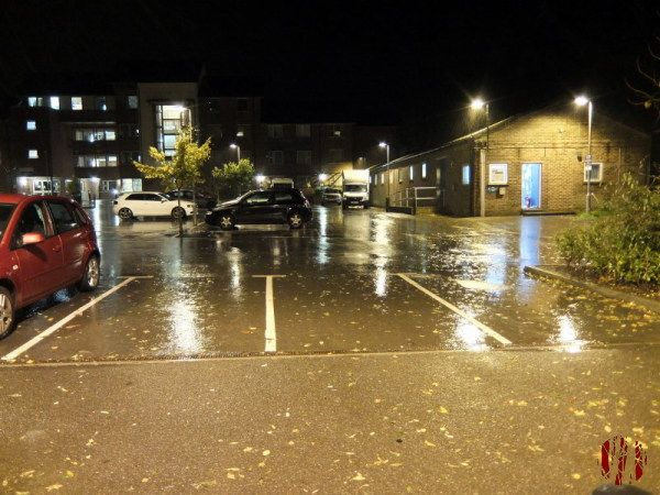 The car park behind the Drill Hall Horsham glistening under the street lights during heavy rain late at night.