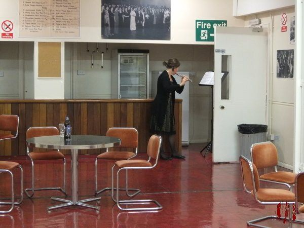A flautist playing in a refreshment area off the Drill Hall where she is performing to utilise the reverb for an effect, and let's face it, a gimmick.
