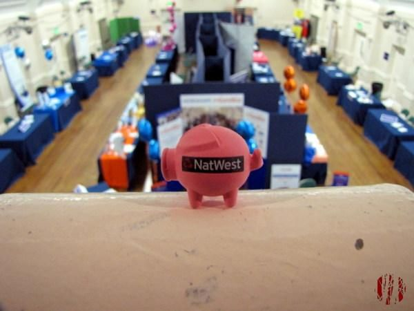 Tiny pink Natwest Pig on a balcony overlooking a business show with stands behind