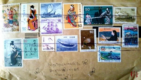 Photography of an envelope which contained cassettes and records with a large number of varied Japanese stamps on it.