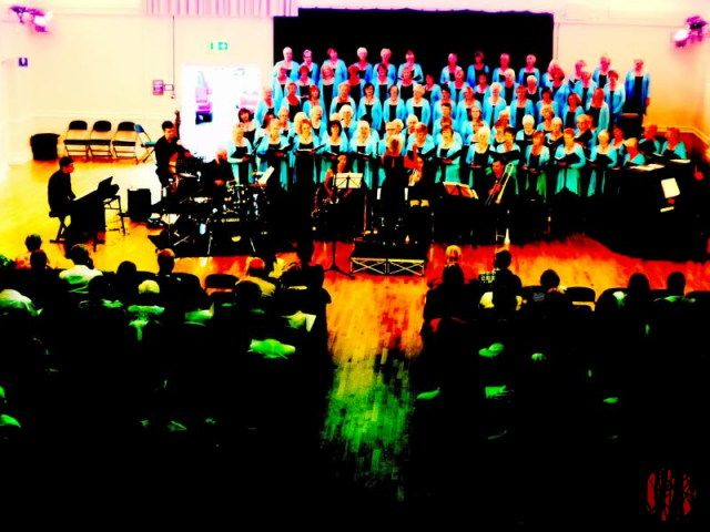 Photograph of a choir and audience taken with a broken camera resulting in odd colours.